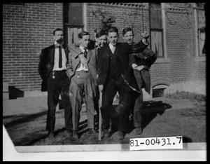 Primary view of object titled 'Five Men in Suits Standing Outside by a Building'.