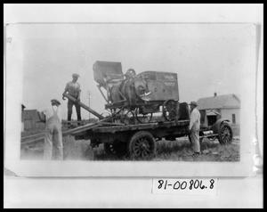 Primary view of object titled 'Men Loading Cotton Gin Equip on Truck'.