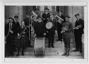 Black and white photo of a group of people standing on stair steps with their band instruments out. At the center front is a man with a giant drum.