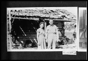 Primary view of object titled 'Man and Woman by Log Cabin'.