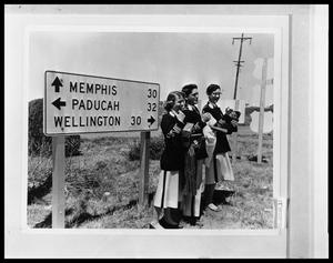 Primary view of object titled 'Three Students Standing Beside Sign'.