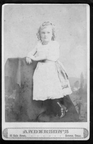 [A little girl wearing a light colored dress.]