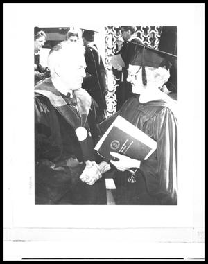 Primary view of object titled 'Man Greeting Woman in Academic Robes at Graduation'.