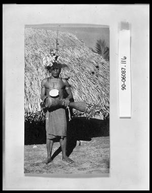 Primary view of object titled 'Native Man by Grass Hut'.