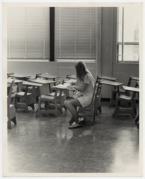 Primary view of object titled '[Photograph of Woman Sitting at Desk]'.