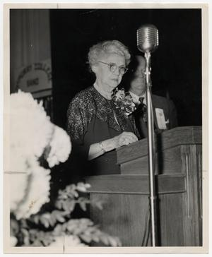 Primary view of object titled '[Photograph of Mrs. J. M. Radford at Podium]'.