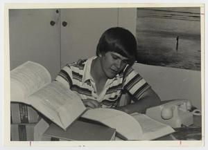 Primary view of object titled '[Photograph of Student Studying Law Books]'.
