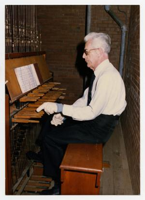 Primary view of object titled '[Photograph of Frank Hinkel Playing Instrument]'.