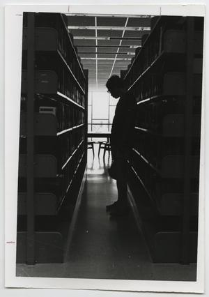 Primary view of object titled '[Photograph of Student in the Stacks at McMurry Library]'.
