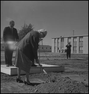 Primary view of object titled '[Photograph of Woman Shoveling Dirt at the Groundbreaking Ceremony for the Jay-Rollins Library]'.