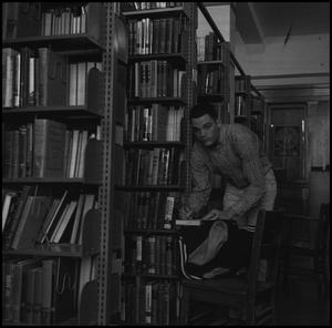 Primary view of object titled '[Photograph of Male Student in Old McMurry Library]'.
