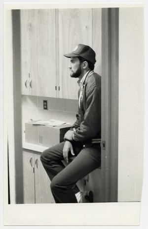 Primary view of object titled '[Photograph of Mark Odom Sitting on Cabinet]'.