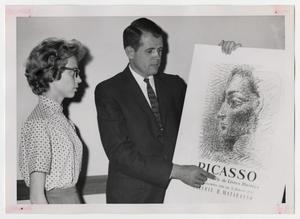 Primary view of object titled '[Photograph of Man and Woman Looking at Picasso Poster]'.