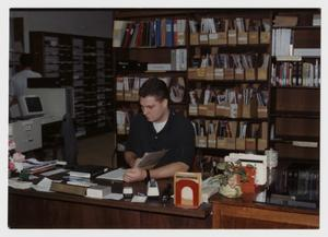 Primary view of object titled '[Photograph of Student at Circulation Desk]'.