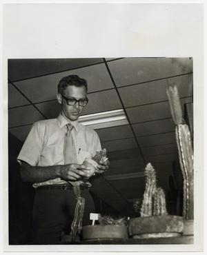Primary view of object titled '[Photograph of Dr. Ben Pilcher With Cactus]'.