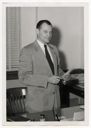 Primary view of object titled '[Photograph of Garnet Gracy Standing Behind Desk]'.
