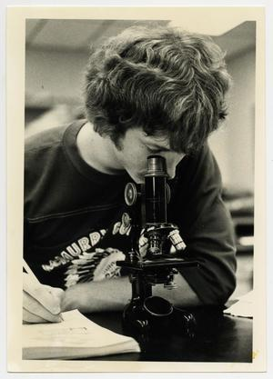 Primary view of object titled '[Photograph of Student With Microscope]'.