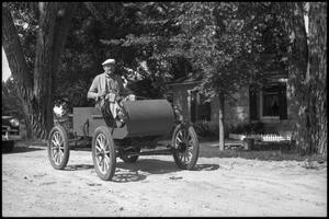 Primary view of object titled '[Photograph of Man Driving Old Car]'.