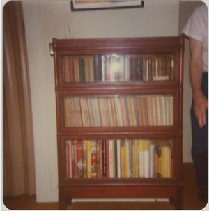 Primary view of object titled '[Photograph of Man Next to Bookshelf]'.