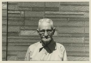 Primary view of object titled '[Photograph of Older Man in Front of Faux Stone]'.