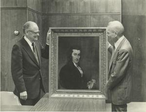 Primary view of object titled '[Photograph of Two Men Holding a Portrait]'.