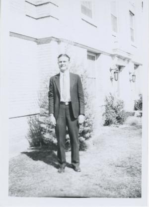 Primary view of object titled '[Photograph of Man in Front of Building]'.