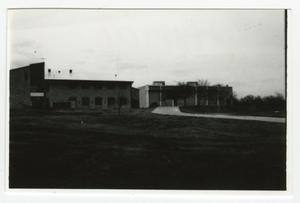 [View of Buildings from Across Grassy Field]