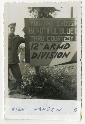 Primary view of object titled '[Norm Wangen Beside 12th Armored Division Sign]'.