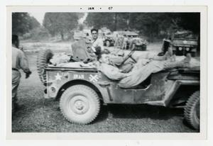 Primary view of object titled '[Photograph of Captain Dave Fairbairn in Jeep]'.