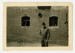 Primary view of object titled '[Photograph of Soldier and Brick Building]'.