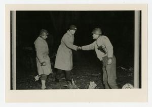 Primary view of object titled '[Two Men Shaking Hands Near Third]'.