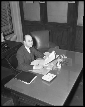 Primary view of object titled '[Marvin Hall Sitting at Desk]'.