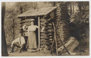 Primary view of object titled '[Postcard with Couple Leaning on a Log Cabin]'.