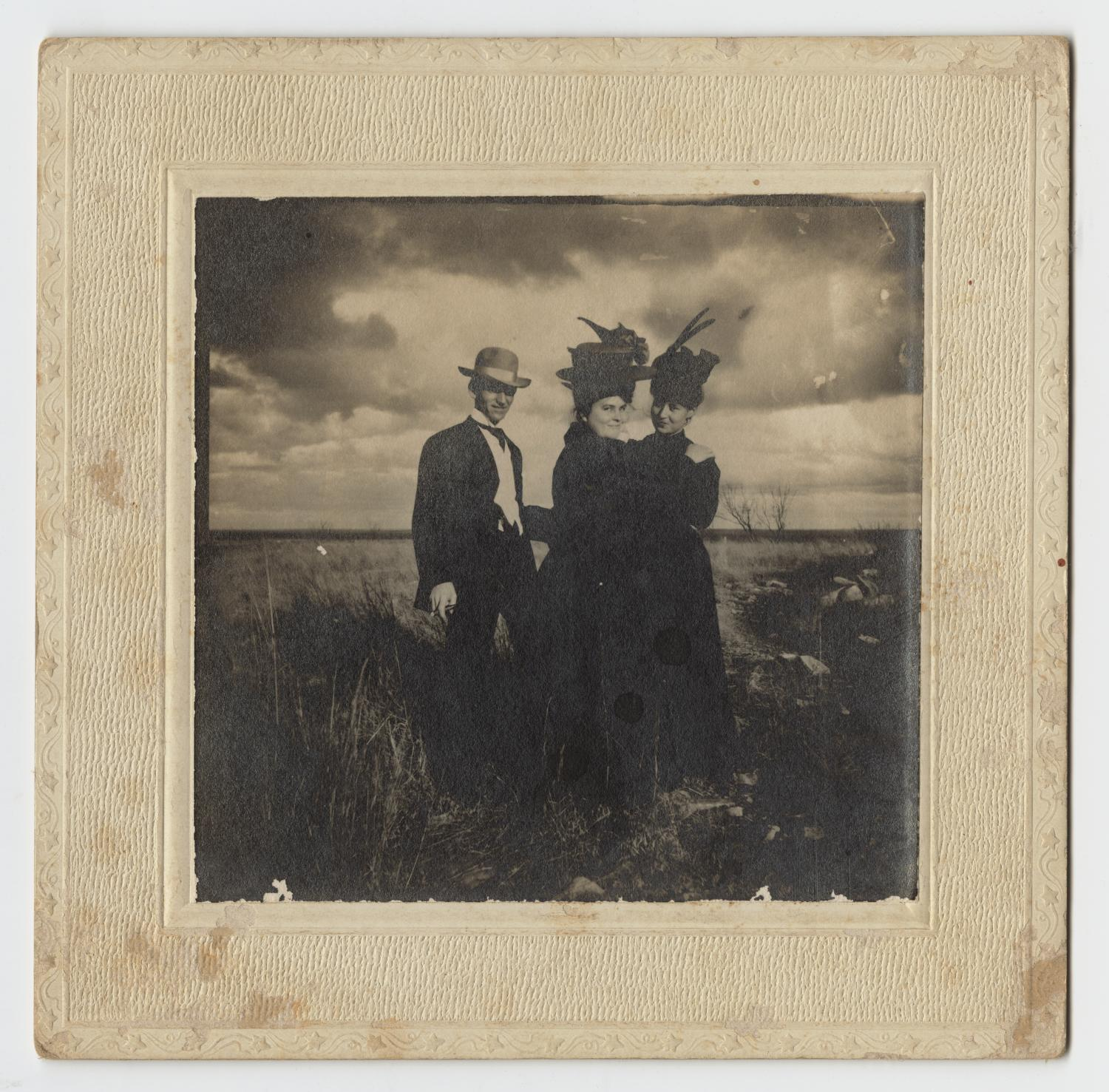 [Harry Wooldridge, Lotta Dibrell, and Mildred McClellan in a Field]                                                                                                      [Sequence #]: 1 of 2