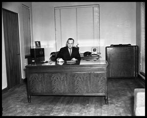 Primary view of object titled '[Portrait of man seated at desk at Covert Automobile Co.]'.