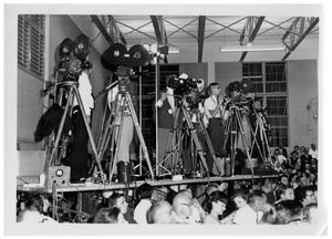 [Cameramen on a Riser Above a Crowd]
