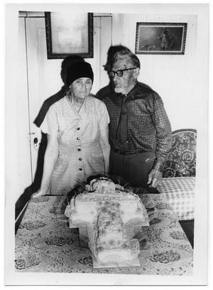 [Mr. and Mrs. Otto Lindig Standing Behind a Cake]