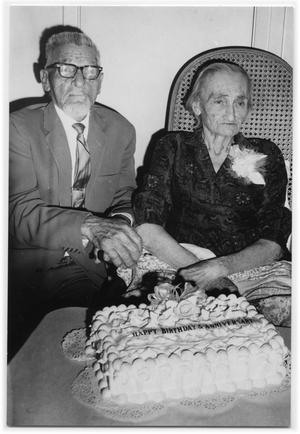 Primary view of object titled '[Otto Lindig and His Wife Sitting at a Table with a Cake]'.
