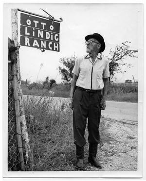 Primary view of object titled '[Otto Lindig Standing Near a Sign for his Ranch]'.