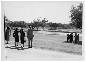 Primary view of object titled '[Helicopter Hovering over a River as People Watch]'.