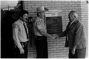 Primary view of object titled '[Sheriff Hugo Klaerner Shaking Hands in Front of Government Building]'.