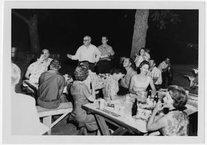 Primary view of object titled '[People Eating at Night on Outdoor Picnic Tables]'.