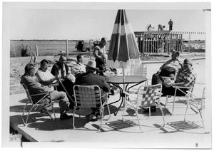 Primary view of object titled '[Men Sitting Around an Outdoor Table]'.