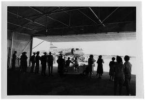 Primary view of object titled '[People Standing in a Building with an Airplane Outside]'.