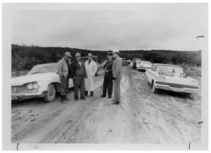 Primary view of object titled '[Men Standing in a Dirt Road that is Lined with Cars]'.