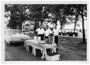 Primary view of object titled '[Three Men Standing at a Picnic Table with Drinks]'.