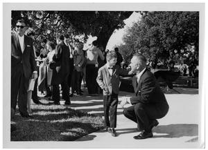 Primary view of object titled '[Lyndon Johnson Kneeling Beside a Young Boy]'.