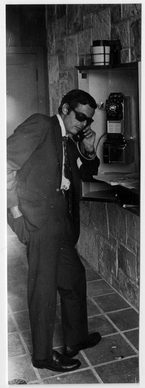 [Man Wearing Sunglasses and Using a Payphone]