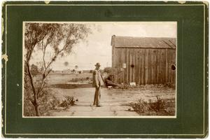 Primary view of object titled '[Nathan L. Bartholomew Standing by at  Barn]'.