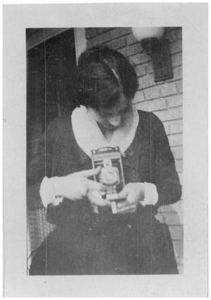 Primary view of object titled '[Woman Examining a Camera]'.